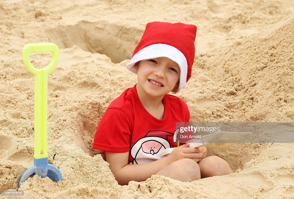 Maddy Swain from England sits inside a hole she has dug for herself at Bondi Beach on December 25, 2012 in Sydney, Australia. Traditionally beaches such as Bondi Beach are popular destinations for tourists and locals alike to celebrate Christmas Day.