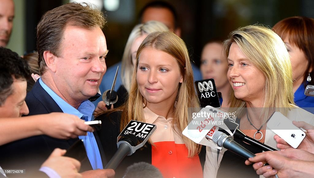 Madeleine Pulver (C) speaks to the media as her father Bill (L) and mother Belinda (R) listen outside of the court in Sydney on November 20, 2012. An investment banker who attached a fake bomb around the neck of Pulver, a Sydney schoolgirl, in a bid to extort money from her wealthy family was jailed for at least 10 years. Paul Peters, who was arrested and extradited from the United States in September last year with the help of the FBI, pleaded guilty earlier this year to aggravated breaking and entering and detaining the teenager for advantage. AFP PHOTO/William WEST