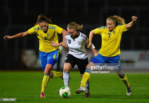 Madeline Gier of Germany is challenged by Julia Wahlberg of Sweden and Fanny Andersson of Sweden during the women's U19 international friendly match...
