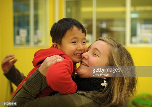 Madelyn Hostetler the biological daughter of American couple Douglas Hostetler and Amanda Hostetler hugs He Chaotong a disabled Chinese orphan they...