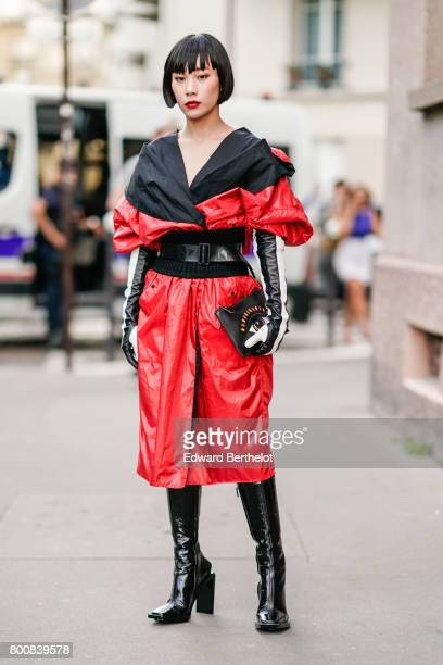 Mademoiselle Yulia wears a black and red ruffled top a black corset a belt a red leather skirt black thigh high boots black and white leather gloves...