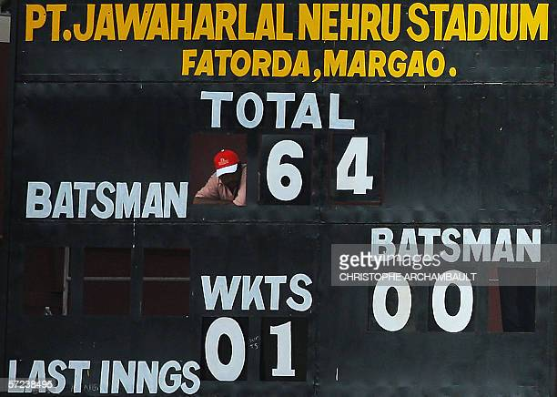 An Indian scoreboard assistant watches play from a vantage point within his workplace during the third OneDay International match between India and...