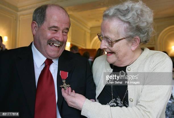 Madge Martin examines her son Charlie Martin's MBE at the British Ambassador's residence in Sandyford Dublin Friday April 7 2006 Mr Martin who...