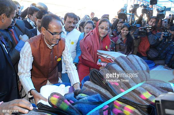Madhya Pradesh Chief Minister Shivraj Singh Chouhan along with his wife donating clothes during an inauguration of weeklong programme of Happiness...
