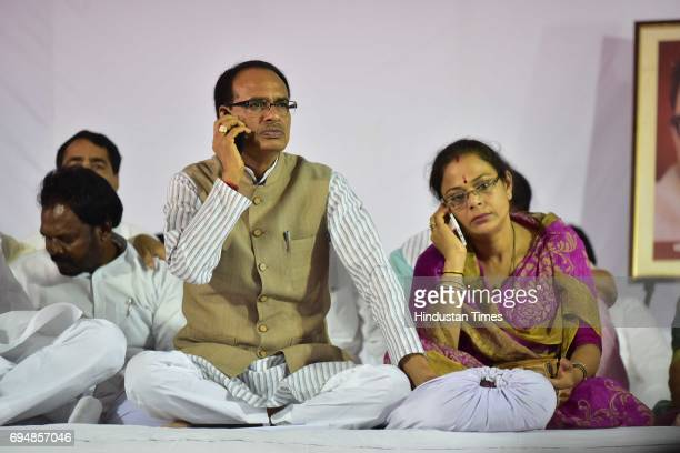 Madhya Pradesh Chief Minister Shivraj Singh Chouhan and his wife Sadhna Singh busy with their cell phones during indefinite fast on June 11 2017 in...