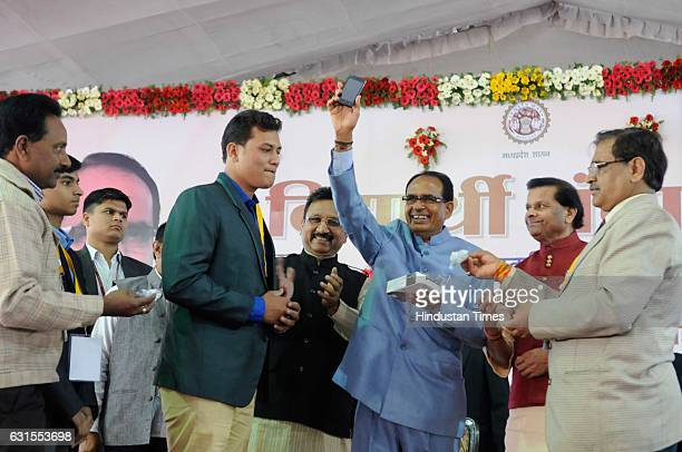 Madhya Pradesh Chief Minister Shivraj Singh Chouhan handing over a smartphone to meritorious student during a 'Vidyarthi Panchayat' at his house on...