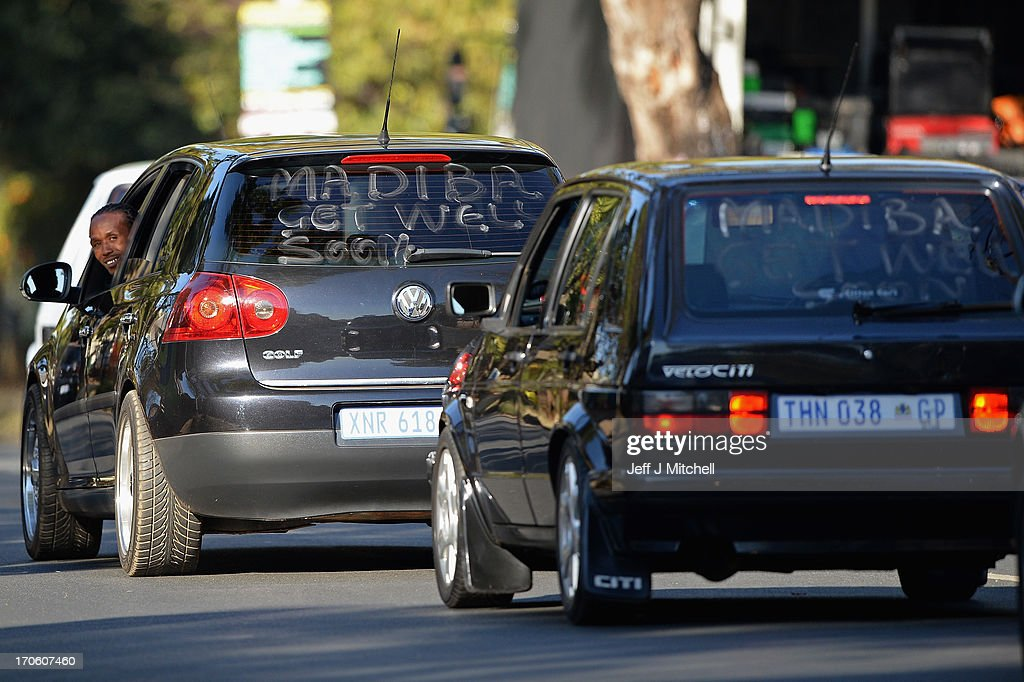 'Madiba get well soon' messages for former South African President Nelson Mandela are seen painted on the rear windows of cars as they drive past Mediclinic Heart Hospital on June 15, 2013 on June 15, 2013 in Pretoria, South Africa. The former South African President and leader of the anti-apartheid movement is spending a seventh night in hospital and is reported to be responding better to treatment for a recurring lung infection.