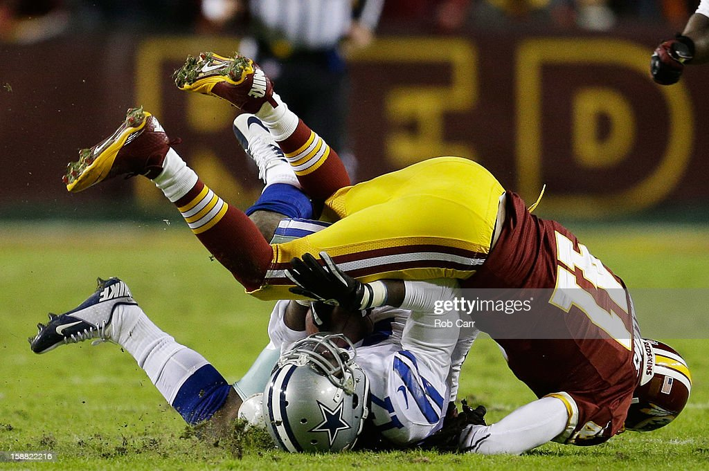 Madieu Williams #41 of the Washington Redskins tackles Dwayne Harris #17 of the Dallas Cowboys after a pass reception in the second quarter at FedExField on December 30, 2012 in Landover, Maryland.