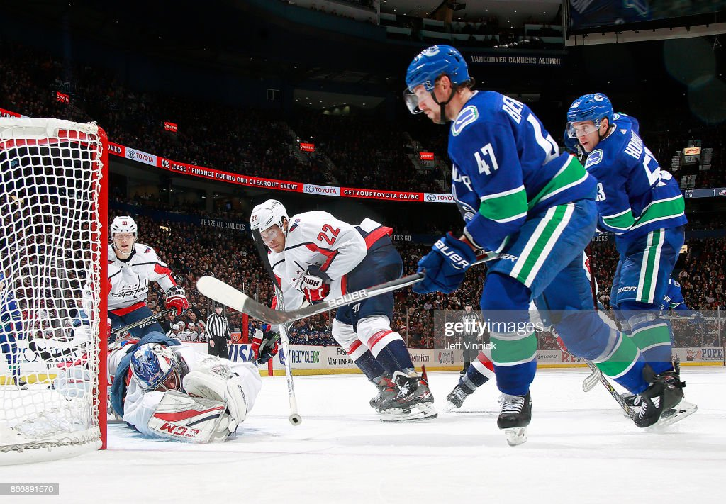 Madison Bowey #22 and Bo Horvat #53 of the Vancouver Canucks look on as Sven Baertschi #47 of the Vancouver Canucks scores on Philipp Grubauer #31 of the Washington Capitals during their NHL game at Rogers Arena October 26, 2017 in Vancouver, British Columbia, Canada. Vancouver won 6-2.