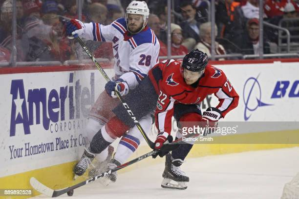Madison Bowey of the Washington Capitals and Paul Carey of the New York Rangers battle for the puck during the third period at Capital One Arena on...