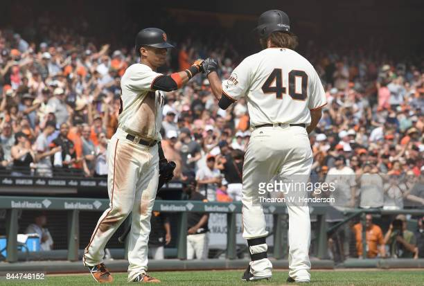 Madison Bumgarner of the San Francisco Giants is congratulated by Gorkys Hernandez after Bumgarner hit a solo home run against the St Louis Cardinals...
