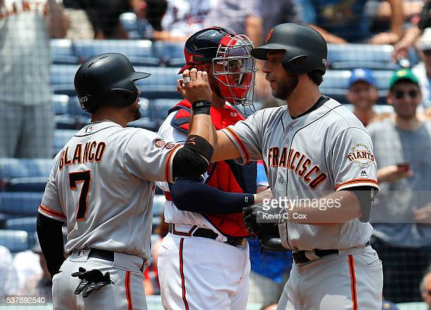 Madison Bumgarner of the San Francisco Giants reacts after hitting a tworun homer in the fifth inning against the Atlanta Braves that also scored...