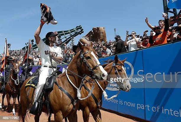Madison Bumgarner of the San Francisco Giants riding a police horse carries the 2014 World Series Championship Flag prior to the start of their game...