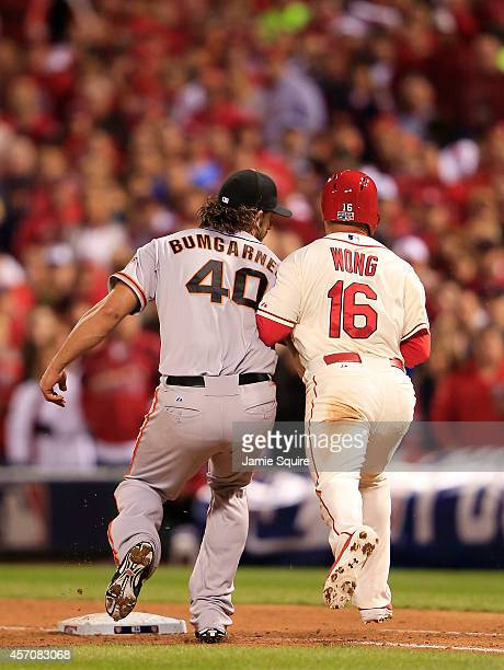 Madison Bumgarner of the San Francisco Giants tags Kolten Wong of the St Louis Cardinals out in the seventh inning during Game One of the National...