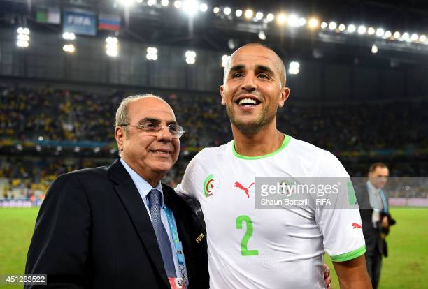 Madjid Bougherra and Algeria Football Association President Mohamed Raouraoua celebrate qualifying for the knock out stage after the 11 draw in the...
