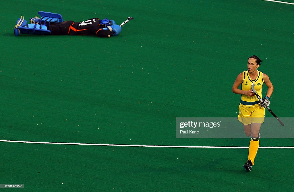 Madonna Blyth of Australia runs back to the midfield after scoring a goal as Farah Ayuni Yahya of Malaysia lies on the ground during the match...
