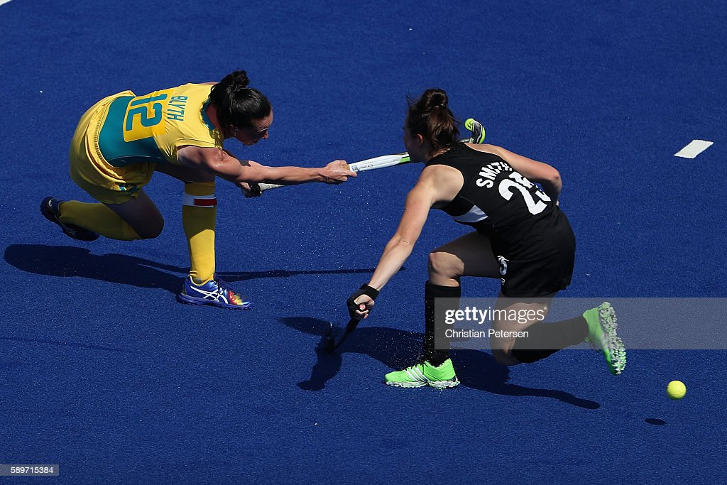 Madonna Blyth of Australia shoots the ball past Kelsey Smith of New Zealand during the second half of the quarter final hockey game on Day 10 of the...