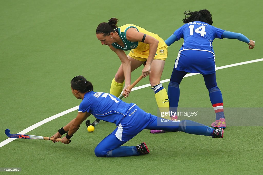 Madonna Blyth of Australia tries to eveade the defence during the Women's preliminary match between Australia and Malaysia at Glasgow National Hockey...