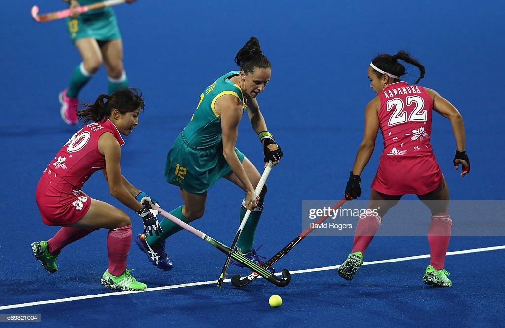 Madonna Blyth of Australlia moves past Minami Shimizu and Motomi Kawamura during the Women's Pool B hockey match between Australia and Japan on Day 8...