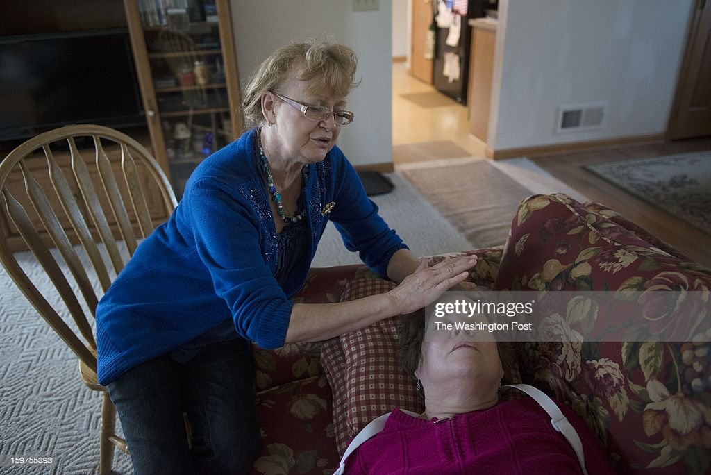 Madonna McDonald prays for Sally Herr in Herr's home on Jan. 16. Herr recently had heart bypass surgery. Herr and her husband, Bill, are active with the Christian church they attend.