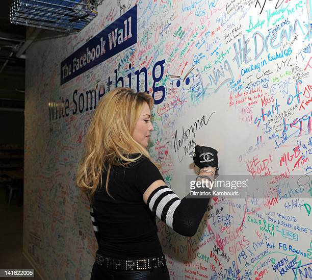 Madonna signs the Facebook wall before her livestream interview with Jimmy Fallon at the Facebook offices on March 24 2012 in New York City