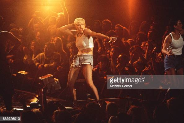 Madonna wearing short cut off jeans combat boots and a tank top cropped to expose her stomach performs before a crowd at Madison Square Garden