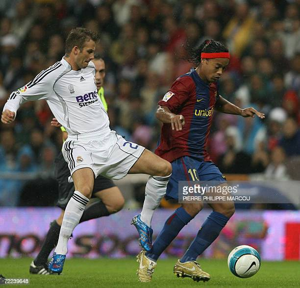 Real Madrid's British midfielder David Beckham tackles Barcelona's Brazilian midfielder Ronaldinho during their Spanish league football match in...