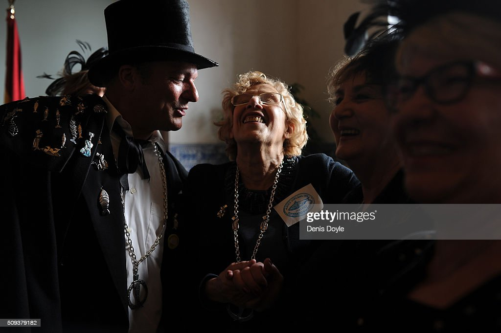 Madrid's Mayor Carmena Manuela laughs with a member of the Brotherhood of the ''Burial of the Sardine'' during a reception for the ''Burial of the Sardine'' procession on February 10, 2016 in Madrid, Spain. The Sardine procession is a centuries-old Spanish tradition made famous by a painting by Spanish artist Francisco de Goya called 'El Entierro de La Sardina'. The mourners hold a mock funeral procession mourning the end of Carnival through the heart of old 'Castizo' Madrid visiting and enjoying the wines and tapas of local taverns.