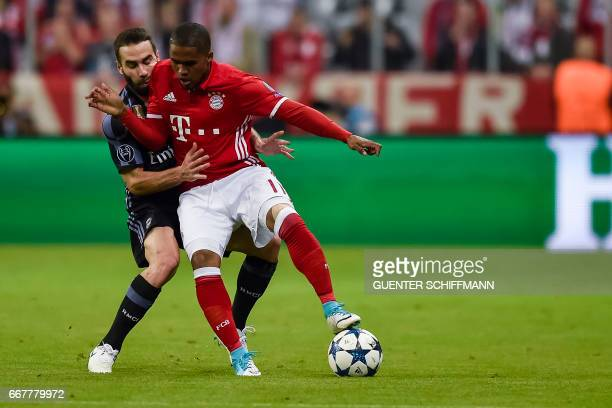 Madrid's Spanish defender Dani Carvajal and Bayern Munich's Brazilian midfielder Douglas Costa vie for the ball during the UEFA Champions League 1st...
