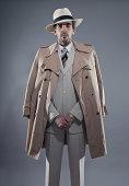 Mafia fashion man wearing white striped suit with beige raincoat and hat. Studio shot.