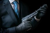 Mafia man or racketeer holds pistol with silencer in hands. Low key photo.