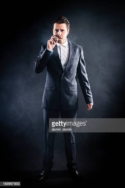 Mafia's man in suit smoking cigar, serious face, slicked hair
