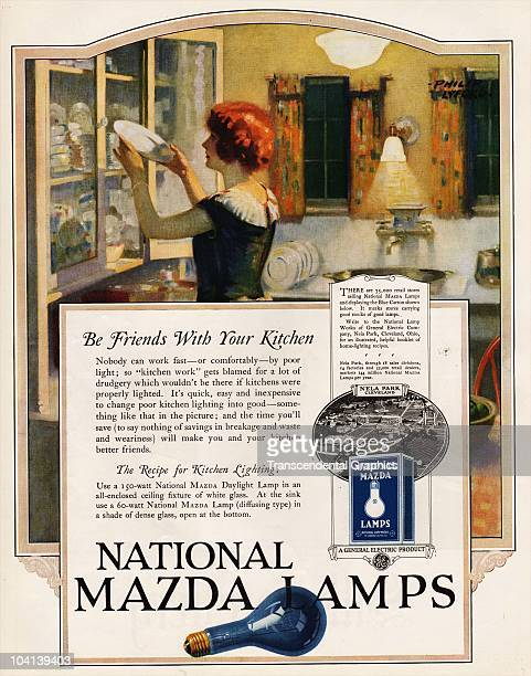 Magazine advertisement for Mazda light bulbs showing a woman replacing china onto her kitchen cabinets by the light of Mazda lightbulbs 1920s Part of...