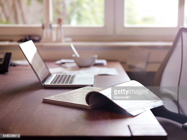 Magazine and laptop on desk