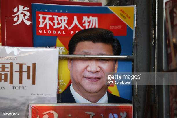 A magazine featuring a photo of Chinese President Xi Jinping is seen at a news stand on a sidewalk in Beijing during the ongoing 19th Communist Party...