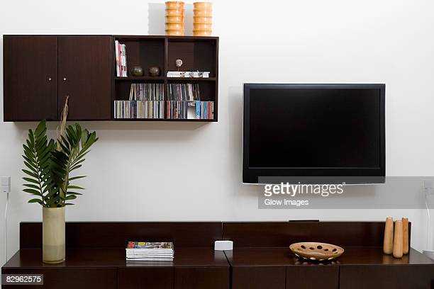 Magazines and a vase on a coffee table in front of a television set