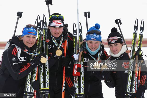 Magdalena Neuner of Germany and her team mates Tina Bachmann Miriam Goessner and Andrea Henkel poses with their goild medals at the victory ceremony...