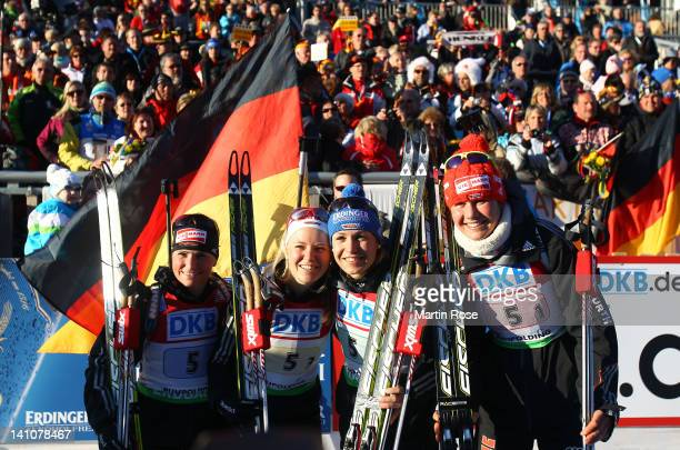 Magdalena Neuner of Germany celebrates winning at the finish area of the Women's 4 x 6km Relay with her team mates Miriam Goessner Andrea Henkel and...