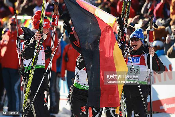 Magdalena Neuner of Germany celebrates winning at the finsih area of the Women's 4 x 6km Relay with her team mates Andrea Henkel Miriam Goessner and...