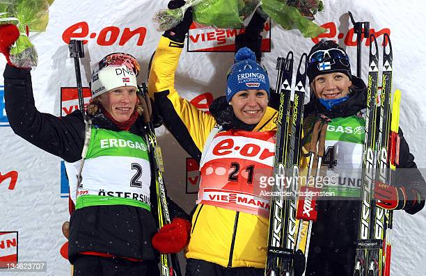 Magdalena Neuner of Germany celebrates with Tora Berger of Norway and Kaisa Maekaeraeinen of Finland at the flower ceremony after the women's 75 km...