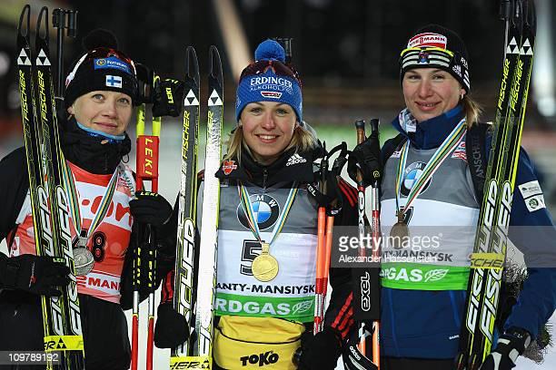 Magdalena Neuner of Germany Kaisa Maekaeraeinen and Anastasiya Kuzmina of Slovakia pose at the victory ceremony after the women's 75km sprint during...