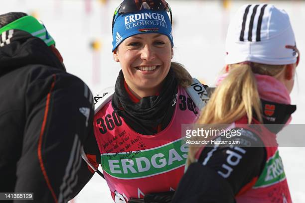 Magdalena Neuner of Germany showsa private note from her team mate Miriam Goessner attached to her bib to her coach Rico Gross during training...