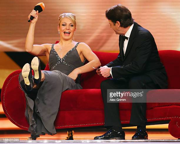 Magdalena Neuner sits on the sofa with host Rudi Cerne after being awarded female 'Athlete of the Year 2012' during a gala at the Kurhaus BadenBaden...
