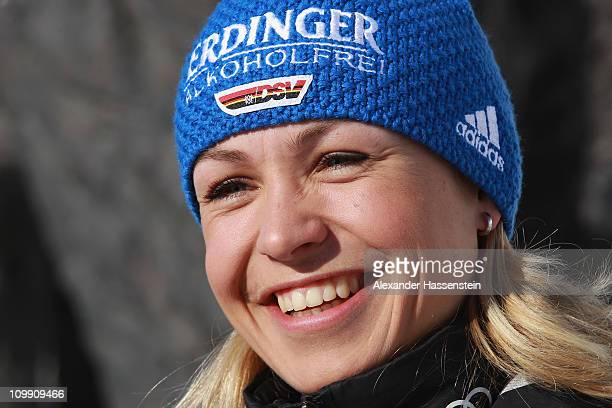 Magdalena Neuner smiles in front of mammoth figures during a photocall of the German Biathlon Woman Team at the Archeopark on March 10 2011 in...