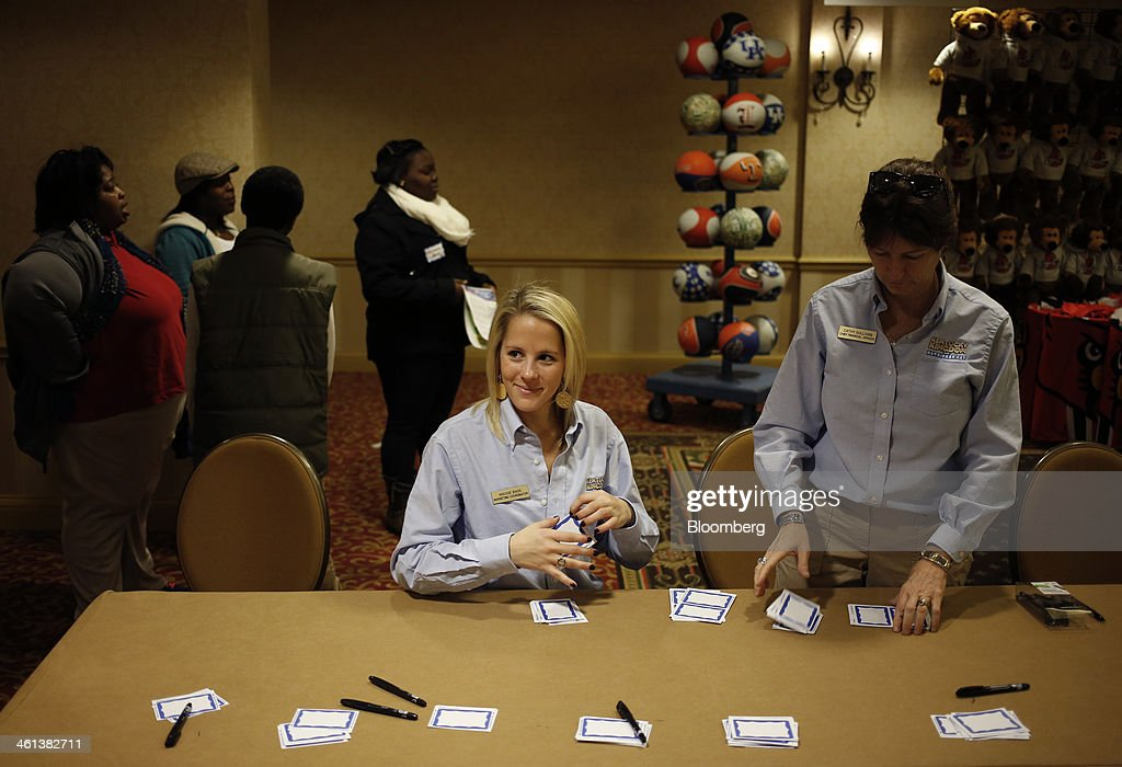 Maggie Bade, marketing coordinator at Kentucky Kingdom Amusement Park , left and Cathy Sullivan, chief financial officer, arrange tags for prospective job applicants during a job fair held by Kentucky Kingdom amusement park to hire seasonal summer workers in Louisville, Kentucky, U.S. on Saturday, Jan. 4, 2014. Companies added more workers than projected in December as U.S. employers grew more optimistic about the prospects for demand, a private report based on payrolls showed Jan. 8. Photographer: Luke Sharrett/Bloomberg via Getty Images