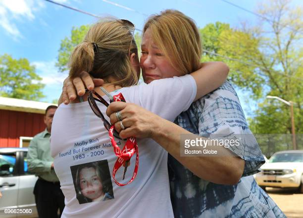 Magi Bish right the mother of Molly Bish cries as she hugs Sarah Stein a private investigator who headed a new search as volunteers using ground...