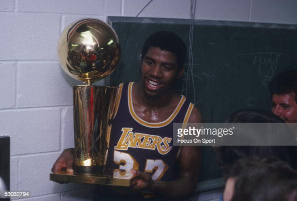 Magic Johnson of the Los Angeles Lakers celebrates with the Walter A Brown championship trophy after winning Game 6 and the series against the...