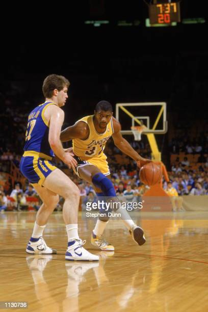 Magic Johnson of the Los Angeles Lakers drives past Chris Mullin of the Golden State Warriors during an NBA game at the Great Western Forum in Los...