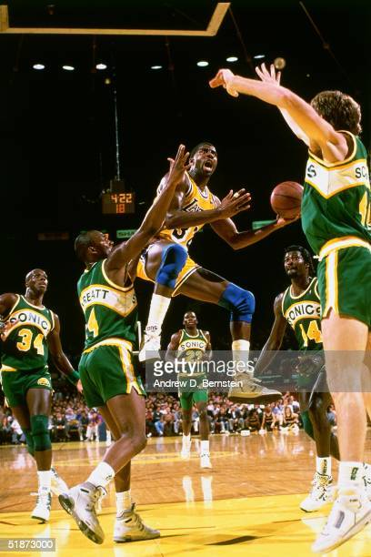 Magic Johnson of the Los Angeles Lakers drives to the basket against the Seattle Supersonics during the NBA game at the Forum in Los Angeles...