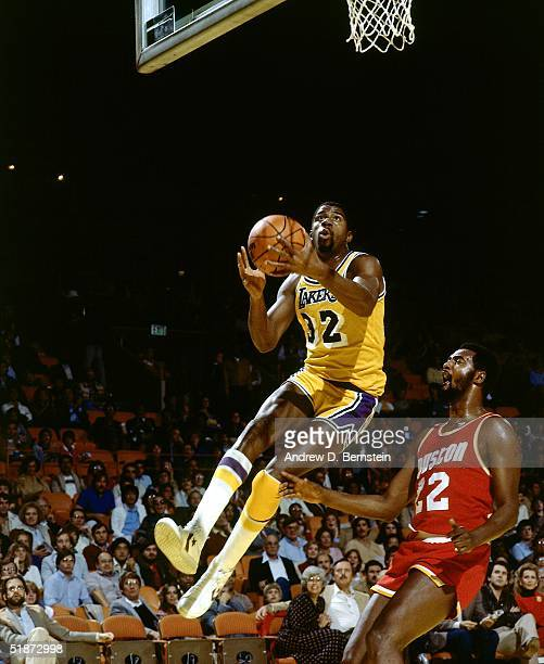 Magic Johnson of the Los Angeles Lakers goes for a layup against the Houston Rockets during the NBA game at the Forum in Los Angeles California NOTE...
